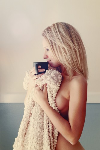 Woman covering her body with nothing but a blanket