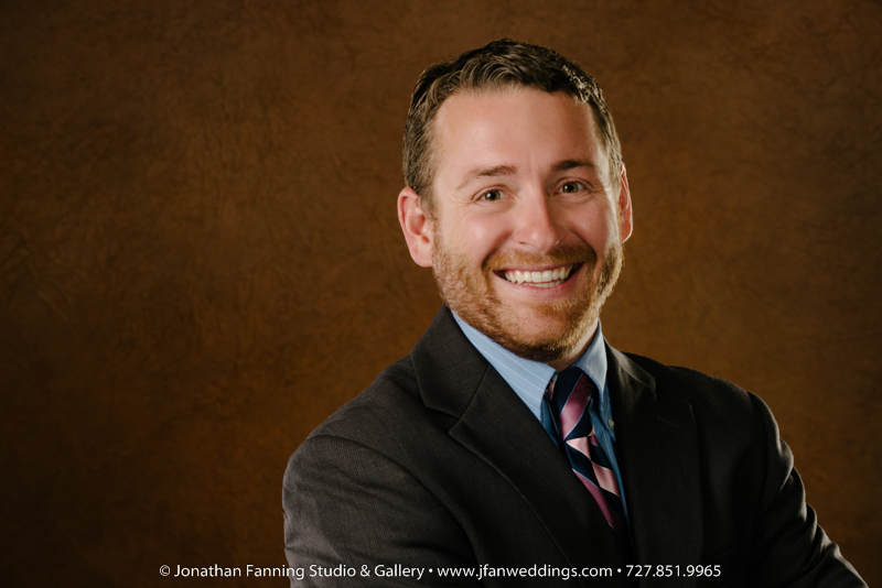 Tampa-area attorney poses for headshot in front of brown backdrop